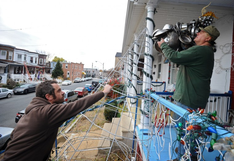 "In preparation for the ""Miracle on 34th Street"" grand lighting, resident Jim Pollock (right) puts the hubcap tree toppper on the 10-foot frame of his hubcap Chritmas tree as Zach Titford assists. (Kenneth K. Lam/Baltimore Sun)"