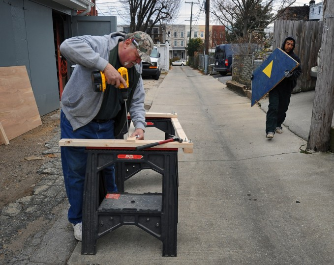 Al Morgan (left), and Vi Nguyen, both residents of the 700 block of W. 34th Street in Hampden, make wooden supports for their light decorations. (Kenneth K. Lam/Baltimore Sun)