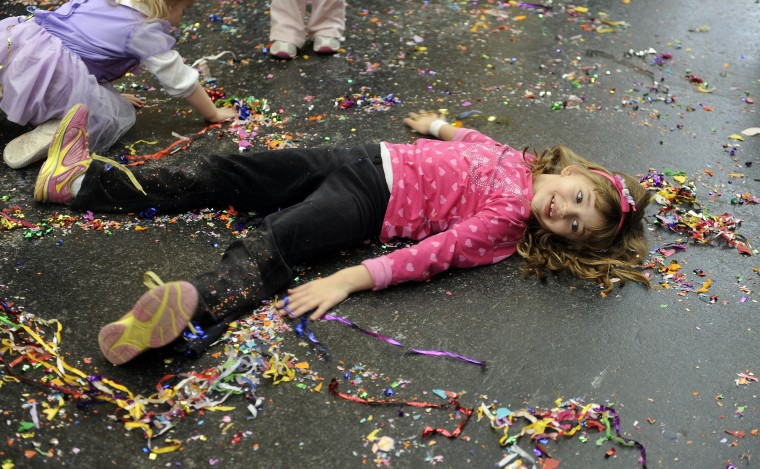 "Mia Saraceno, 6 of Parkville, makes a confetti angel at the Port Discovery Children's Museum, where 2014 was celebrated 12 hours early during a ""Royal Masquerade"" party and New Year's countdown. (Barbara Haddock Taylor/Baltimore Sun)"