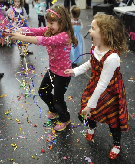 "Mia Saraceno, 6, left of Parkville and Ellie Conradi, 5, right of Towson, play with confetti at the Port Discovery Children's Museum, where 2014 was celebrated 12 hours early during a ""Royal Masquerade"" party and New Year's countdown. (Barbara Haddock Taylor/Baltimore Sun)"