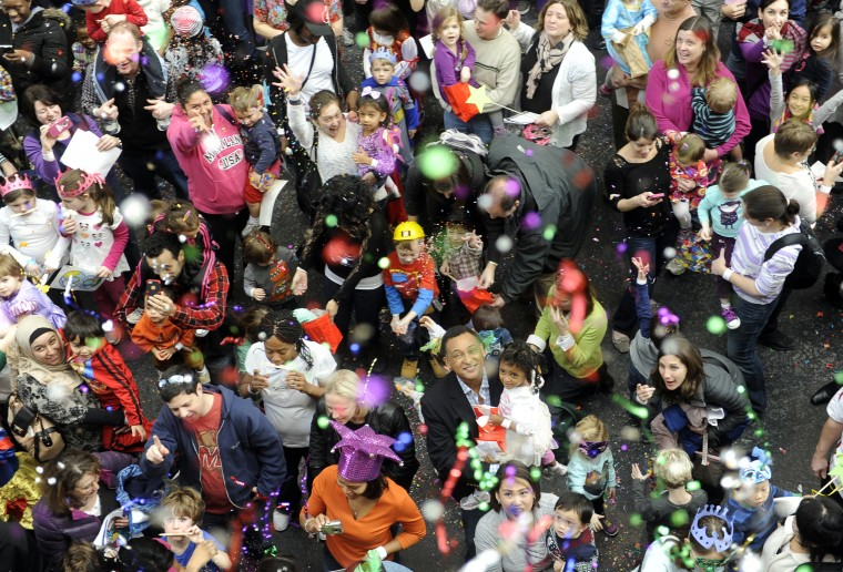 "Confetti falls on the crowd at noon at the Port Discovery Children's Museum, where 2014 was celebrated 12 hours early during a ""Royal Masquerade"" party and New Year's countdown. (Barbara Haddock Taylor/Baltimore Sun)"