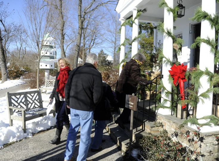 "Emily Emerick, left, executive director, greets guests as they enter ""Christmas Through the Ages, "" a tour of Christmas decorations at the Manor House at Ladew Gardens. (Barbara Haddock Taylor/Baltimore Sun)"