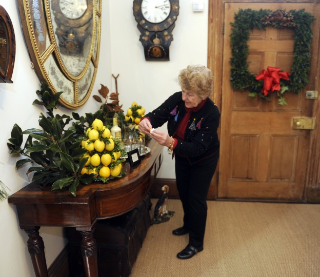 "Germaine Vadas, senior staff docent at Ladew Topiary Gardens, turns on votive lights in a hall for the ""Christmas Through the Ages"" tour at the Manor House at Ladew Gardens. (Barbara Haddock Taylor/Baltimore Sun)"