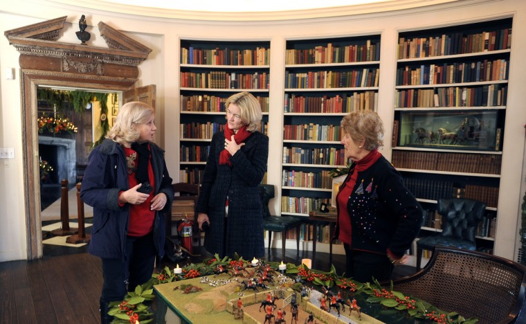"Left to right in the Oval Library at the Manor House at Ladew Gardens: Dot Bucharewicz (volunteer), Emily Emerick (executive director) and Germaine Vadas (senior docent). The home is decorated in a ""Christmas Through the Ages"" theme. (Barbara Haddock Taylor/Baltimore Sun)"