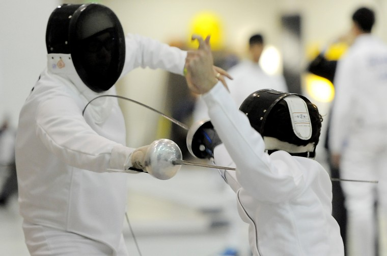 Ron Santos, left, Forest Hill, Maryland Fencing Club, and Jake Mickey, Boston, Boston Fencing Club, attack in a seeding round. (Kim Hairston/Baltimore Sun)