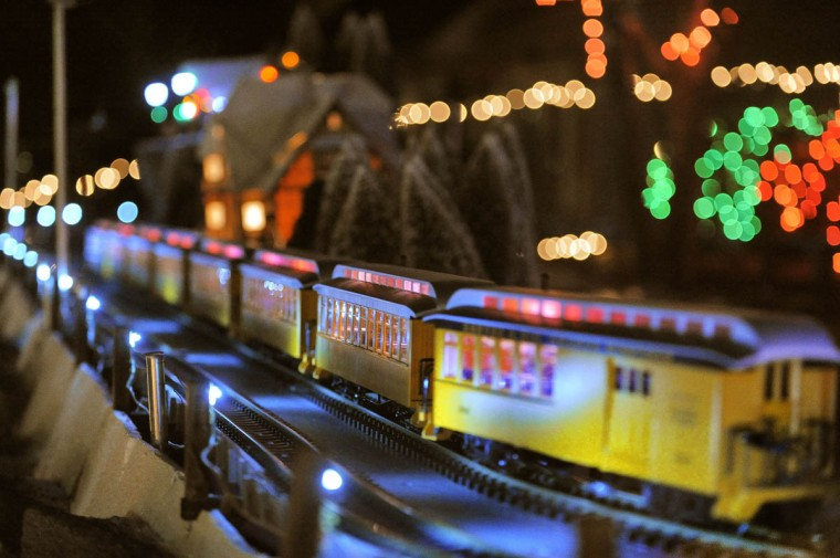 Passenger cars glow in the night while heading out of Beaverton, a holiday N-gauge train village. (Karl Merton Ferron/Baltimore Sun Staff)