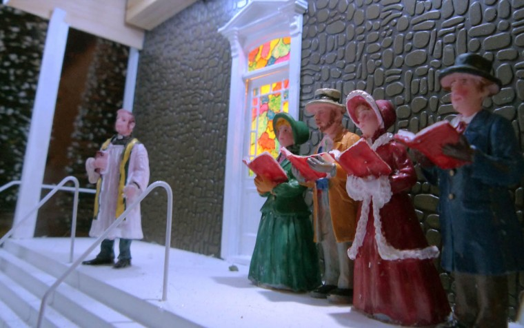 At the town's church, the pastor stands by as carolers sing at the holiday resort of Beaverton Cliffs, a holiday G-gauge train village created on the front yard of John and Kim Beverly. (Karl Merton Ferron/Baltimore Sun Staff)