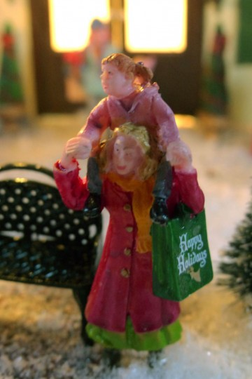 A child rides piggy back as her mother carries gifts. (Karl Merton Ferron/Baltimore Sun Staff)