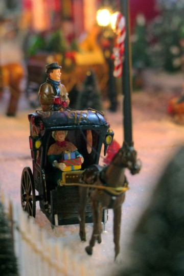 A horse-drawn carriage bears a woman with presents. (Karl Merton Ferron/Baltimore Sun Staff)