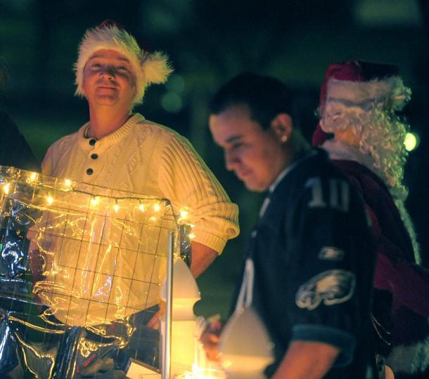 John Beverly wears a Santa hat as people look at the village of Beaverton Cliffs. (Karl Merton Ferron/Baltimore Sun Staff)