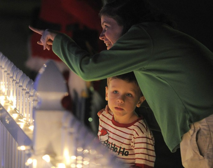 """Max Lemke, 4 of Odenton gazes at the trains rolling by as he stands next to his mother Rebekah Lemke, who points at """"Beaverton,"""" a holiday N-gauge train village created on the front yard of John and Kim Beverly. (Karl Merton Ferron/Baltimore Sun Staff)"""