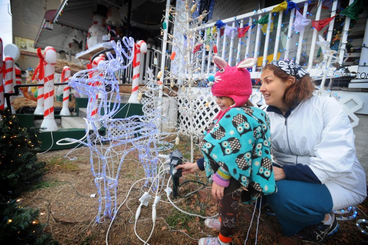 "Elaine Doyle-Gillespie tests lights in her yard with the help of her 2-year-old daughter Piper. Residents illuminated the celebrated ""Miracle on 34th Street"" holiday display on Nov. 30 this year. (Kenneth K. Lam/Baltimore Sun)"