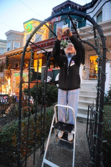 Sharon Burke hangs plastic mistletoe on the arch leading to her home on 34th Street. (Kenneth K. Lam/Baltimore Sun)