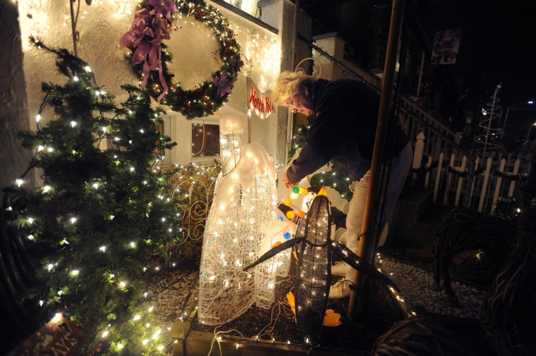 "Sharon Burke makes last-minute adjustments to the lights outside her home before the ""Miracle on 34th Street"" grand lighting. (Kenneth K. Lam/Baltimore Sun)"