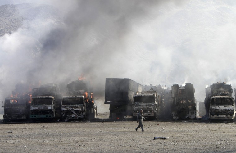 An Afghan policeman walks near burning NATO supply trucks after what police officials say was an attack by militants in the Torkham area near the Pakistani-Afghan border in Jalalabad Province December 18, 2013. The attack killed one police officer and wounded three others, according to the police. (Parwiz/Reuters)