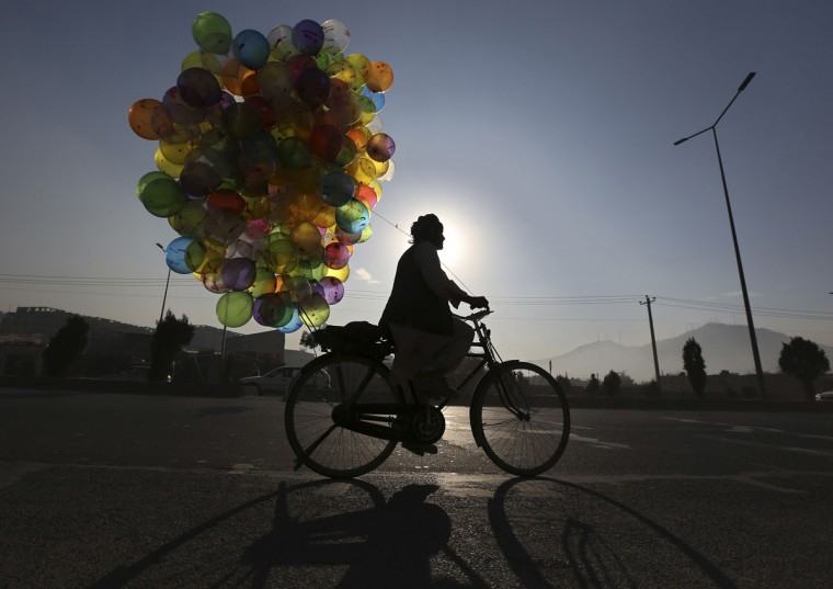 An Afghan man selling balloons rides on his bicycle in Kabul December 3, 2013. (Omar Sobhani/Reuters)