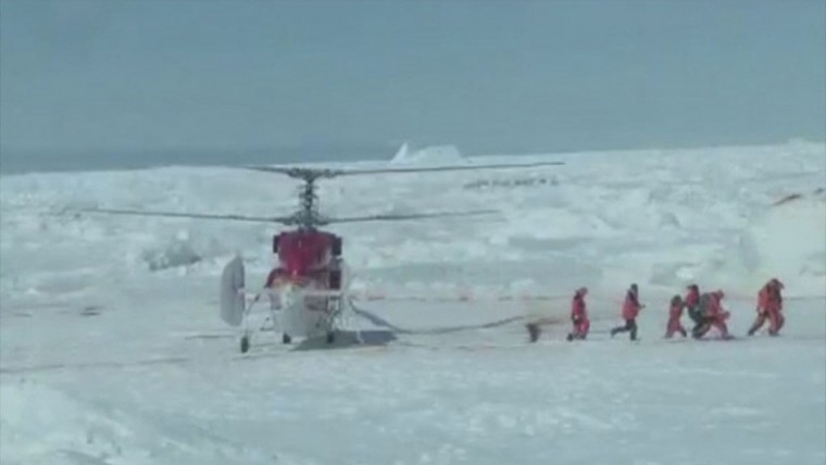 Rescue workers make their way from a helicopter to the Russian ship Akademik Shokalskiy, which has been trapped in Antarctic ice since Christmas Eve, at Commonwealth Bay in East Antarctica, 100 nautical miles (185 km) east of French Antarctic station Dumont D'Urville and about 1,500 nautical miles (2,800km) south of Australia's southern island state of Tasmania, in this still image taken from video shot by expedition leader Chris Turney, Professor of Climate Change at the University of New South Wales, on January 2, 2014. The Chinese helicopter has reached a Russian ship stranded in Antarctica for nine days and is beginning to pick up 52 passengers who spent Christmas and the New Year trapped in ice, Turney said on Thursday. (REUTERS/Chris Turney via youtube.com/user/christurney)