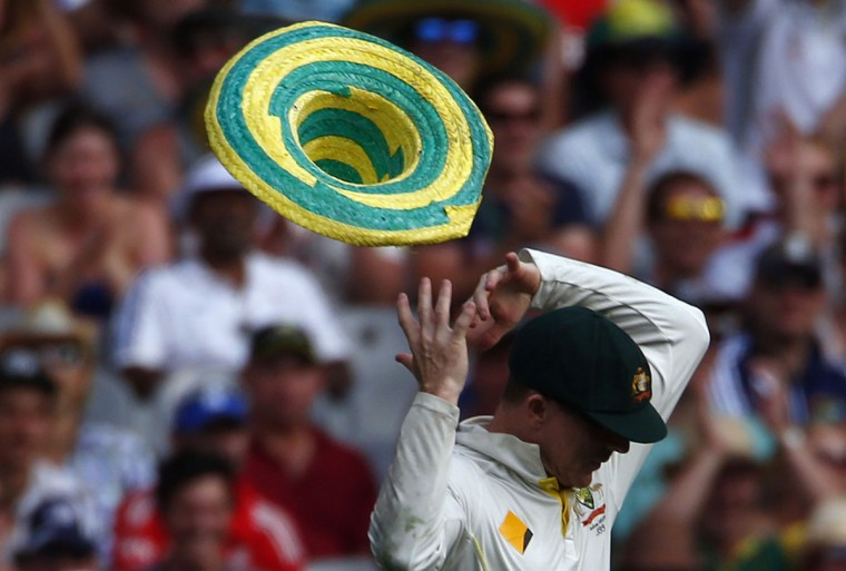 A hat that blew onto the field, is blown off the head of Australia's Chris Rogers after he put it on during the first day of the fourth Ashes cricket test against England, at the Melbourne cricket ground December 26, 2013. (REUTERS/David Gray)