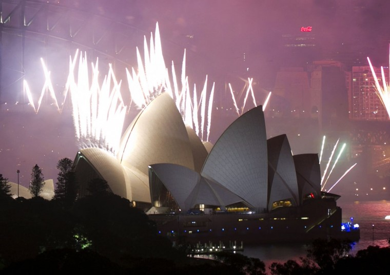 fireworks explode off the sydney opera house at midnight ushering in the new year