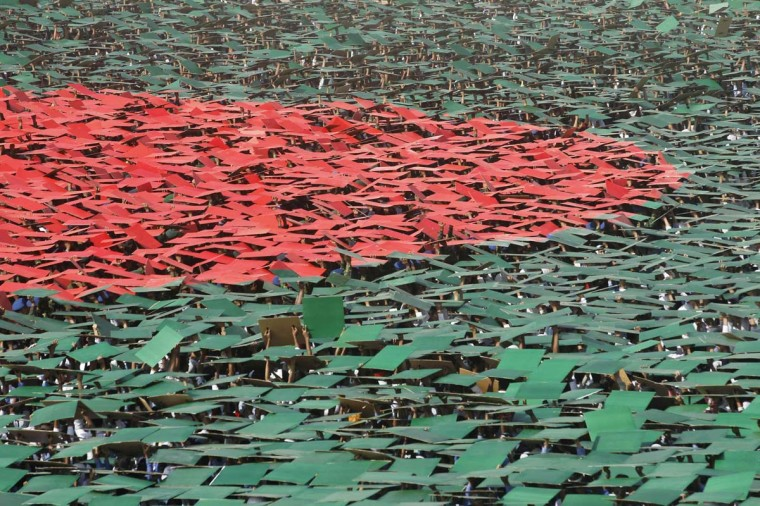 Volunteers prepare to form a large flag of Bangladesh as the nation celebrates National Victory Day at the National Parade ground in Dhaka December 16, 2013. According to the organizers, 27,117 volunteers formed a large human national flag for six minutes and sixteen seconds as they attempted to set a new Guinness world record. Bangladesh won independence from Pakistan on December 16, 1971, following a nine-month guerrilla war which cost millions of lives. (Andrew Biraj/Reuters)