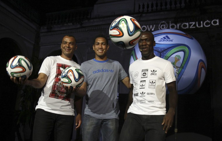 From left, former Brazilian soccer player Cafu, current Brazilian soccer player Hernane and Dutch soccer player Clarence Seedorf show the official match ball for the 2014 World Cup during its presentation at Lage Park in Rio de Janeiro. (Reuters photo)