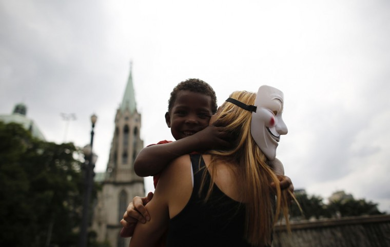 A woman, wearing a Guy Fawkes mask, and from the Anonymous movement embraces a homeless child during a Christmas street celebration in downtown Sao Paulo December 24, 2013. Members of Black Bloc group and the Anonymous movement provided food and clothes to homeless people during the celebration. (REUTERS/Nacho Doce)