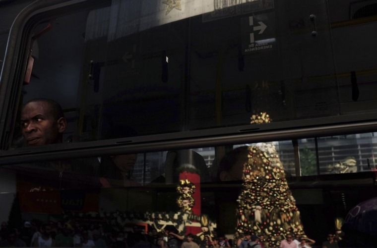 A man looks out of a window on a public transport bus in which a Christmas tree and decorations are reflected at the financial centre on Sao Paulo's Avenida Paulista December 26, 2013. (REUTERS/Nacho Doce)