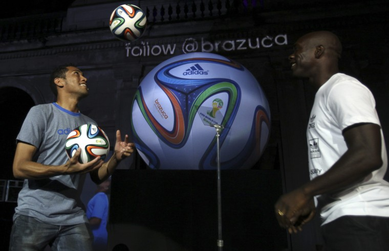 Brazilian soccer player Hernane, left, and Dutch soccer player Clarence Seedorf play with the official match ball for the 2014 World Cup named Brazuca during its presentation at Lage Park in Rio de Janeiro. (Reuters photo)