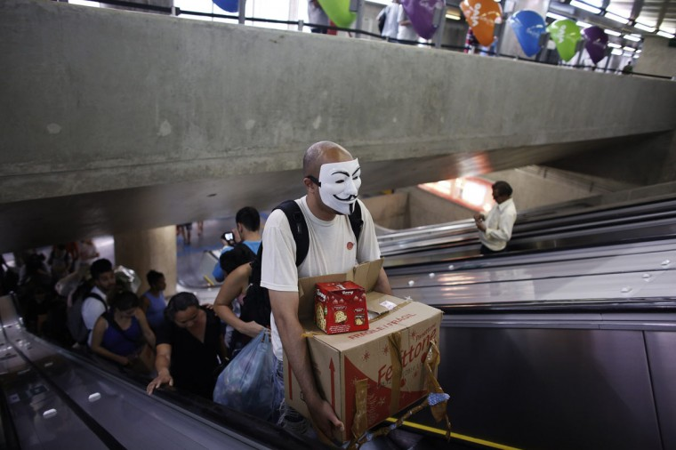 A member from the Anonymous movement stands on an escalator at a subway station with food to give to homeless people as part of a Christmas street celebration, in downtown Sao Paulo December 24, 2013. Members of Black Bloc group and the Anonymous movement provided food and clothes to homeless people during the celebration. (REUTERS/Nacho Doce)