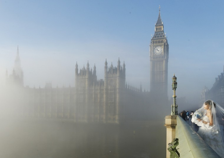 A bride poses for a photograph on Westminster Bridge as the fog clears in central London. (Olivia Harris/Reuters)