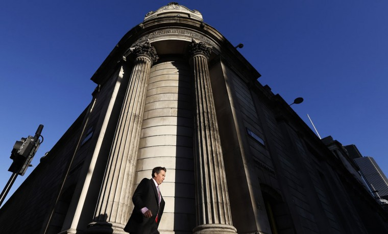 A man walks past the Bank of England in London December 20, 2013. Standard & Poor's confirmed Britain's last remaining triple A credit rating on Friday, but said it could cut the top-notch ranking if the country's economic recovery was not sustained. (REUTERS/Suzanne Plunkett)