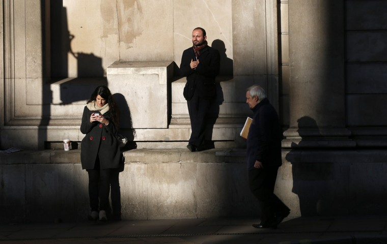 People stand in the sun outside the Bank of England in London December 20, 2013. Standard & Poor's confirmed Britain's last remaining triple A credit rating on Friday, but said it could cut the top-notch ranking if the country's economic recovery was not sustained. (REUTERS/Suzanne Plunkett)
