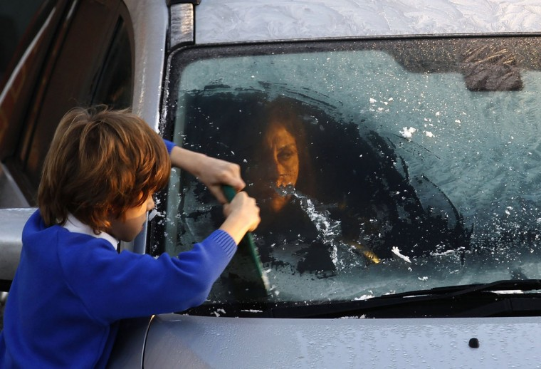A young boy scrapes ice off his mother's car windscreen on a frosty morning in west London December 20, 2013. (REUTERS/Luke MacGregor)