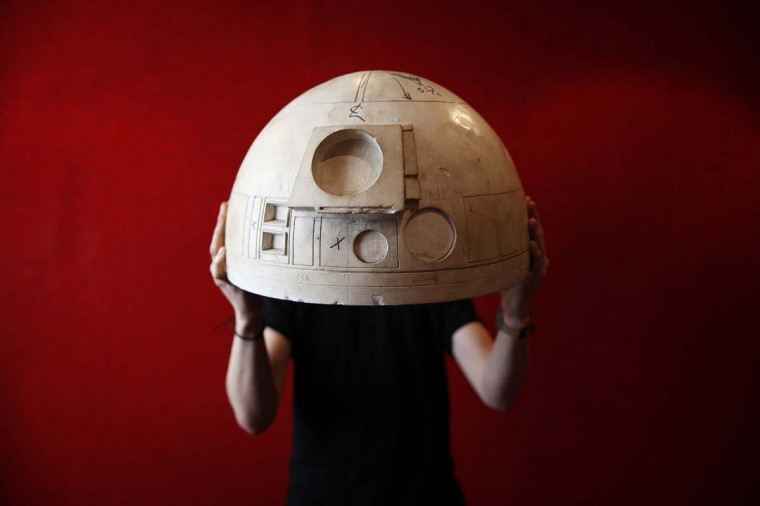 Olie Williams of Bonhams displays a working mould for the first R2D2 Star Wars character in central London, December 12, 2013. The mould, is expected to fetch between £6000-£8000 ($9,780-$13,040), when it goes under the hammer on December 18. REUTERS/Andrew Winning