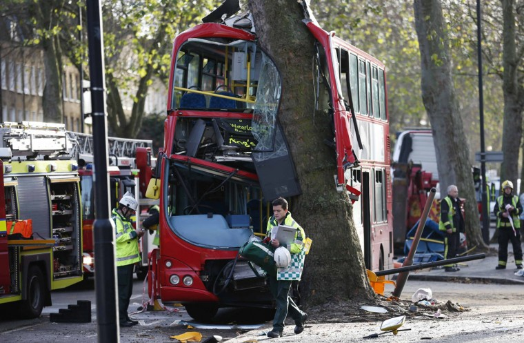 A members of the emergency services walks in front of a bus which crashed into a tree in Kennington, south London, December 20, 2013. 23 people were injured, two seriously, in the crash according to the Metropolitan Police. (REUTERS/Suzanne Plunkett)