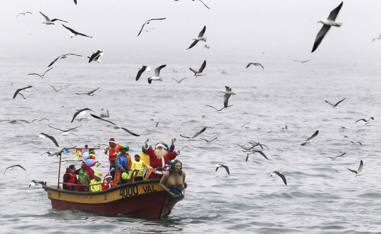 Ruben Torres, dressed in a Santa Claus outfit, wave to people from a boat with fishermen on Christmas Eve along the coast of Valparaiso city, about 121 km (75 miles) northwest of Santiago, December 24, 2013. Every year, fishermen in Valparaiso organize a Santa Claus boat trip as people wait on the shore to receive their Christmas presents and well-wishes. (REUTERS/Eliseo Fernandez)