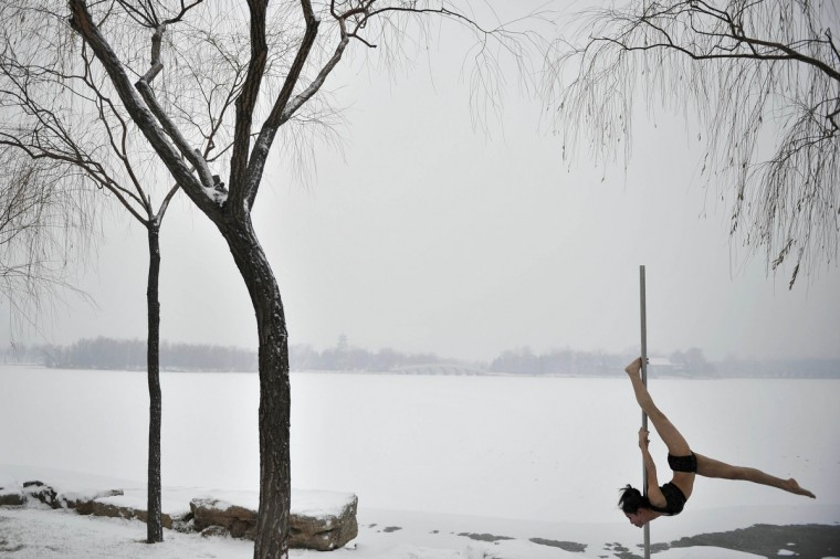 A member of China's national pole dance team performs at a park after the city's first snow this winter in Tianjin. (China Daily/Reuters)