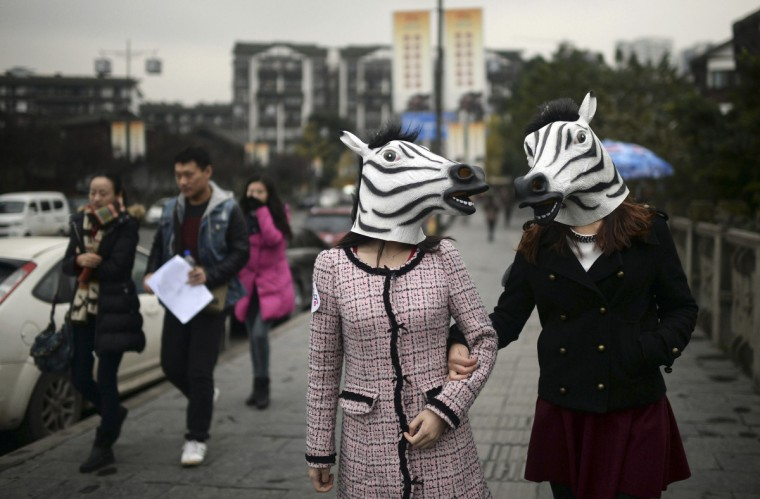 Participants wearing zebra head masks wander down a street as part of an artistic performance ahead of the Year of the Horse in Chinese zodiac in Chongqing Municipality. The performance aims to bring good luck to everyone for the upcoming year, according to local media.(Reuters)