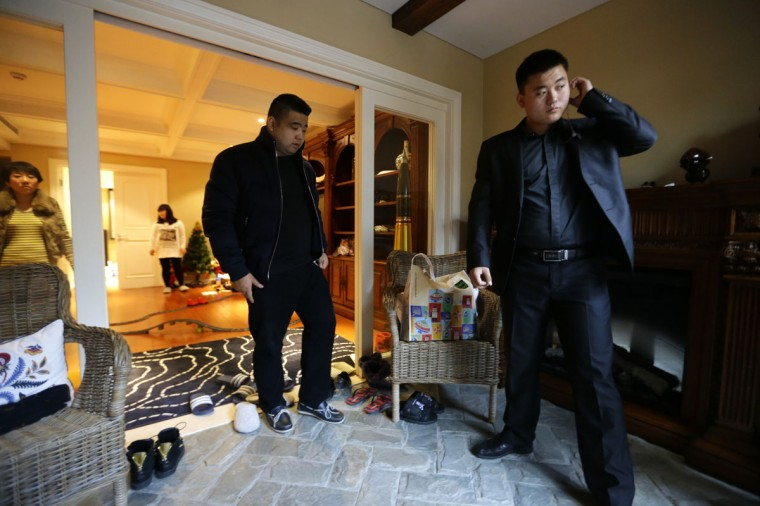 Bodyguard Han, who was hired from Tianjiao Special Guard/Security Consultant, checks his earphone as his employer Zhang prepares to leave home on the outskirts of Beijing December 15, 2013. Former Chinese soldier Chen Yongqing has big ambitions for his bodyguard training school Tianjiao, which he says is China's first professional academy to train former soldiers and others as personal security guards. Chen charges 500,000 yuan ($82,400) a year for each protector as China's rich and famous look to bolster their safety and sense of importance. (REUTERS/Jason Lee/December 15, 2013)