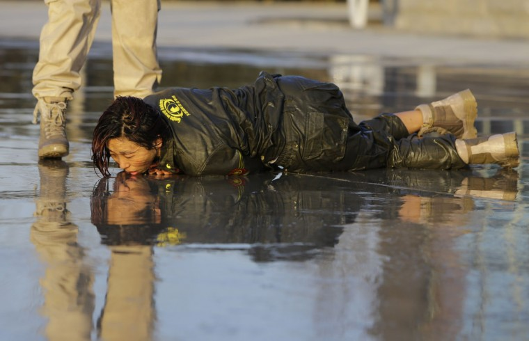 A female trainee lies on the ground after being drenched with water during Tianjiao Special Guard/Security Consultant training on the outskirts of Beijing December 1, 2013. Former Chinese soldier Chen Yongqing has big ambitions for his bodyguard training school Tianjiao, which he says is China's first professional academy to train former soldiers and others as personal security guards. Chen charges 500,000 yuan ($82,400) a year for each protector as China's rich and famous look to bolster their safety and sense of importance. (REUTERS/Jason Lee/December 1, 2013)