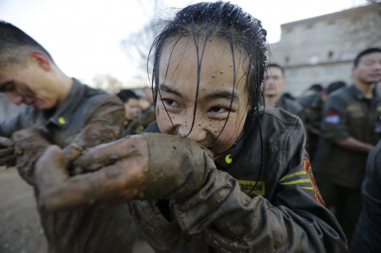A female student opens her cufflinks with her teeth, after crawling through mud at Tianjiao Special Guard/Security Consultant camp on the outskirts of Beijing December 12, 2013. Former Chinese soldier Chen Yongqing has big ambitions for his bodyguard training school Tianjiao, which he says is China's first professional academy to train former soldiers and others as personal security guards. Chen charges 500,000 yuan ($82,400) a year for each protector as China's rich and famous look to bolster their safety and sense of importance. (REUTERS/Jason Lee/December 12, 2013)