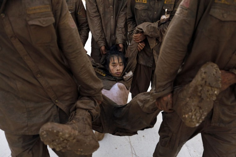 Students carry a female trainee who has fallen into a stupor during high intensity training at Tianjiao Special Guard/Security Consultant camp on the outskirts of Beijing December 1, 2013. Former Chinese soldier Chen Yongqing has big ambitions for his bodyguard training school Tianjiao, which he says is China's first professional academy to train former soldiers and others as personal security guards. Chen charges 500,000 yuan ($82,400) a year for each protector as China's rich and famous look to bolster their safety and sense of importance. (REUTERS/Jason Lee/December 1, 2013)