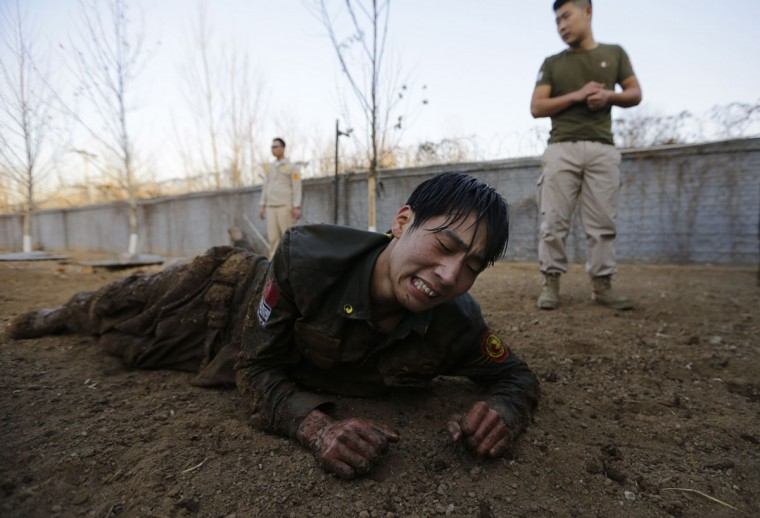 A student reacts as he crawls on the ground during Tianjiao Special Guard/Security Consultant training on the outskirts of Beijing December 1, 2013. Former Chinese soldier Chen Yongqing has big ambitions for his bodyguard training school Tianjiao, which he says is China's first professional academy to train former soldiers and others as personal security guards. Chen charges 500,000 yuan ($82,400) a year for each protector as China's rich and famous look to bolster their safety and sense of importance. (REUTERS/Jason Lee/December 1, 2013)