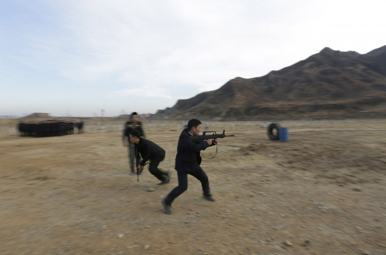 Students take part in training at a field managed by the military during Tianjiao Special Guard/Security Consultant training on the outskirts of Beijing December 14, 2013. Former Chinese soldier Chen Yongqing has big ambitions for his bodyguard training school Tianjiao, which he says is China's first professional academy to train former soldiers and others as personal security guards. Chen charges 500,000 yuan ($82,400) a year for each protector as China's rich and famous look to bolster their safety and sense of importance. (REUTERS/Jason Lee/December 14, 2013)
