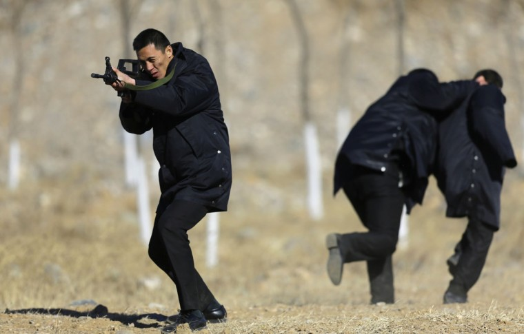 Students practice protecting employers at a shooting training field managed by the military during Tianjiao Special Guard/Security Consultant training on the outskirts of Beijing December 14, 2013. Former Chinese soldier Chen Yongqing has big ambitions for his bodyguard training school Tianjiao, which he says is China's first professional academy to train former soldiers and others as personal security guards. Chen charges 500,000 yuan ($82,400) a year for each protector as China's rich and famous look to bolster their safety and sense of importance. (REUTERS/Jason Lee)