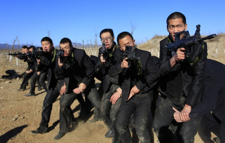 Students holding replica 95 semi-automatic rifles practice protecting their employers at a shooting training field managed by the military during Tianjiao Special Guard/Security Consultant training on the outskirts of Beijing December 14, 2013. Former Chinese soldier Chen Yongqing has big ambitions for his bodyguard training school Tianjiao, which he says is China's first professional academy to train former soldiers and others as personal security guards. Chen charges 500,000 yuan ($82,400) a year for each protector as China's rich and famous look to bolster their safety and sense of importance. (REUTERS/Jason Lee/December 14, 2013)