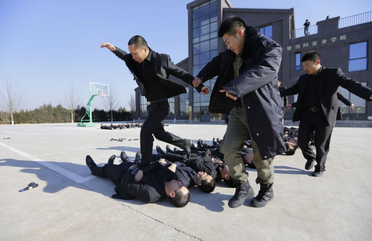 Students run over the bodies of fellow trainees at the Tianjiao Special Guard/Security Consultant training camp on the outskirts of Beijing December 11, 2013. Former Chinese soldier Chen Yongqing has big ambitions for his bodyguard training school Tianjiao, which he says is China's first professional academy to train former soldiers and others as personal security guards. Chen charges 500,000 yuan ($82,400) a year for each protector as China's rich and famous look to bolster their safety and sense of importance. (REUTERS/Jason Lee/December 11, 2013)