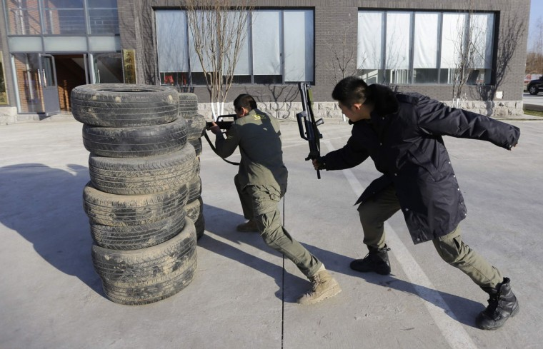 An instructor hits a trainee with a replica 95 semi-automatic rifle during training at the Tianjiao Special Guard/Security Consultant training camp on the outskirts of Beijing December 11, 2013. Former Chinese soldier Chen Yongqing has big ambitions for his bodyguard training school Tianjiao, which he says is China's first professional academy to train former soldiers and others as personal security guards. Chen charges 500,000 yuan ($82,400) a year for each protector as China's rich and famous look to bolster their safety and sense of importance. (REUTERS/Jason Lee/December 11, 2013)
