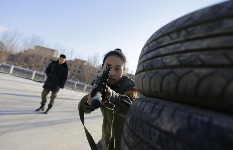 A student aims a replica 95 semi-automatic rifle during training at the Tianjiao Special Guard/Security Consultant training camp on the outskirts of Beijing December 11, 2013. Former Chinese soldier Chen Yongqing has big ambitions for his bodyguard training school Tianjiao, which he says is China's first professional academy to train former soldiers and others as personal security guards. Chen charges 500,000 yuan ($82,400) a year for each protector as China's rich and famous look to bolster their safety and sense of importance. (REUTERS/Jason Lee/December 11, 2013)