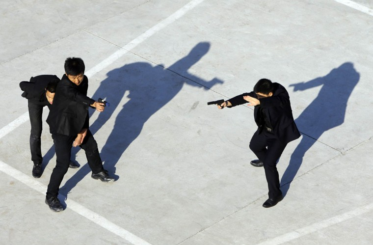 Trainees point replica pistols as they take part in a training session at the Tianjiao Special Guard/Security Consultant training camp on the outskirts of Beijing, December 11, 2013. Former Chinese soldier Chen Yongqing has big ambitions for his bodyguard training school Tianjiao, which he says is China's first professional academy to train former soldiers and others as personal security guards. Chen charges 500,000 yuan ($82,400) a year for each protector as China's rich and famous look to bolster their safety and sense of importance. (REUTERS/Jason Lee/December 11, 2013)